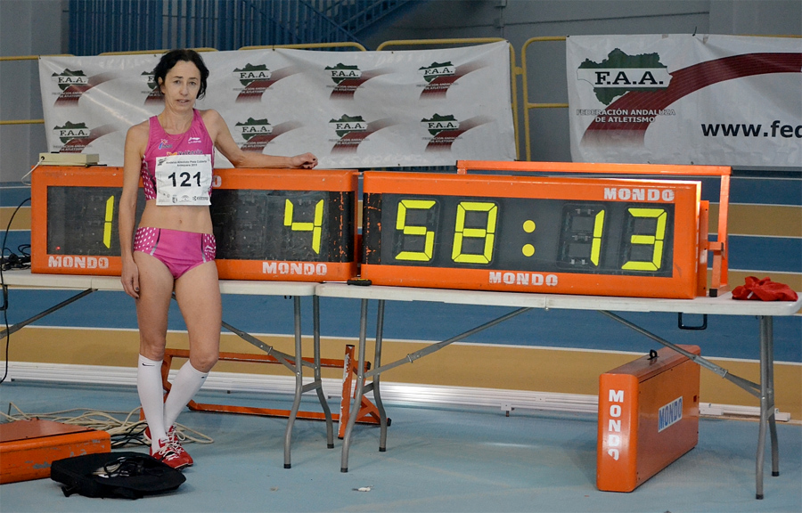 Aurora, looking winded but buff in bikini briefs, poses with her indoor WR time.