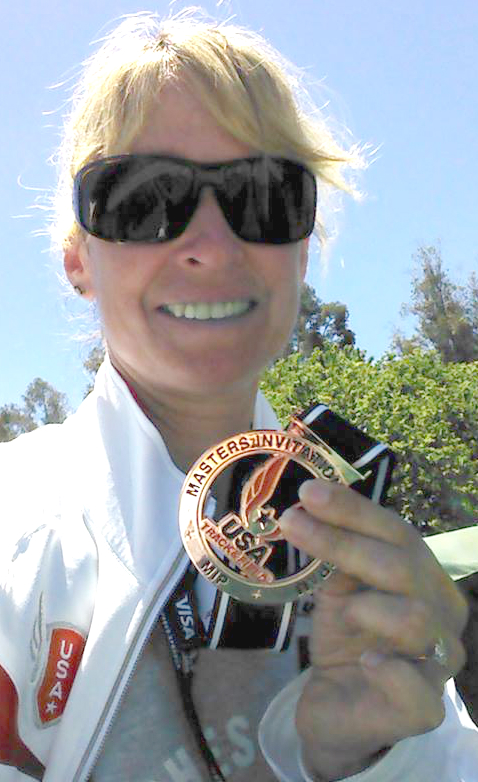 Colleen Barney shows off snazzy medal from 100 exhibition at open nationals.