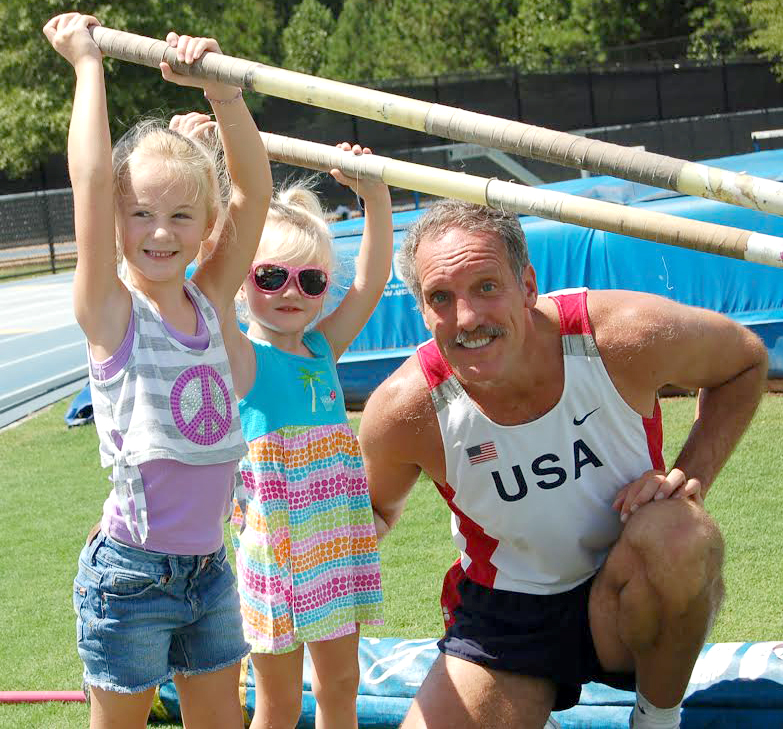 Eric Negley gives a vaulting tip to grand-daughters Braelynn and Kinslee.