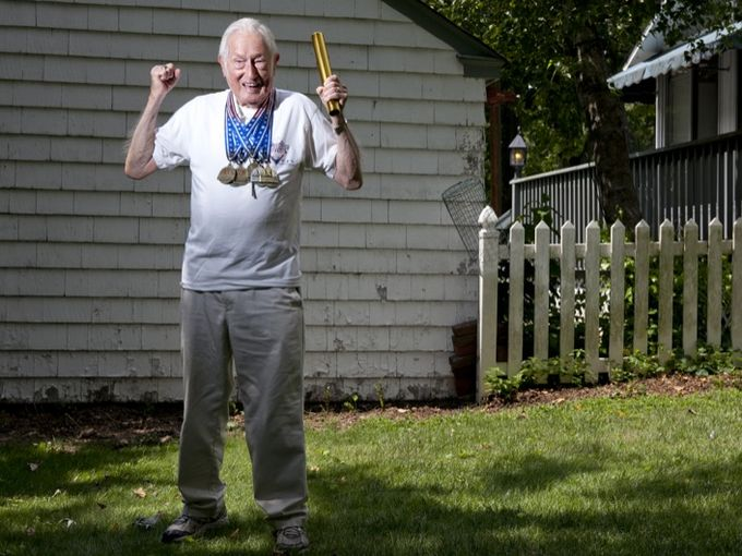 Champ outside home with his N.C. medals. Photo by Douglas Bovitt of Courier-Post