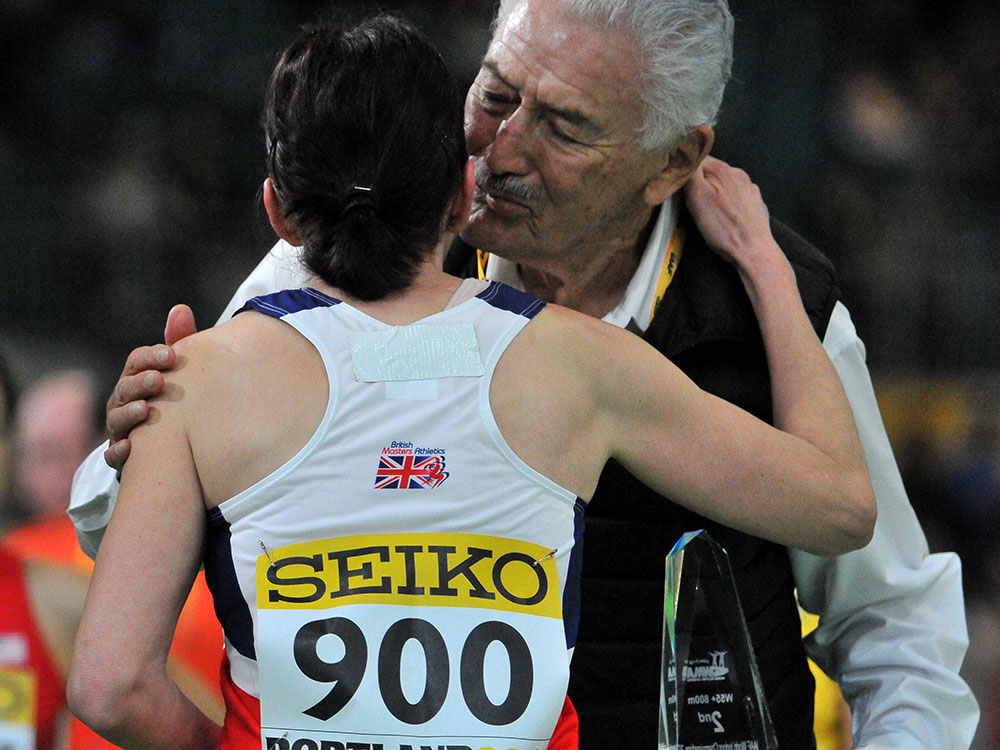 IAAF's Cesar Moreno Bravo kisses Britain's Karen Brooks after her third-place finish in W55 800.
