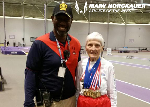 Mary posed with her medals and a meet official.