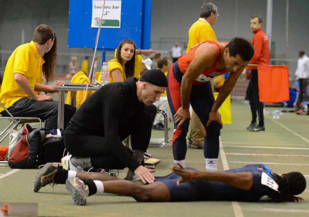 Karl Hawke checks on U.S. teammate Antonio after injury during triple jump.