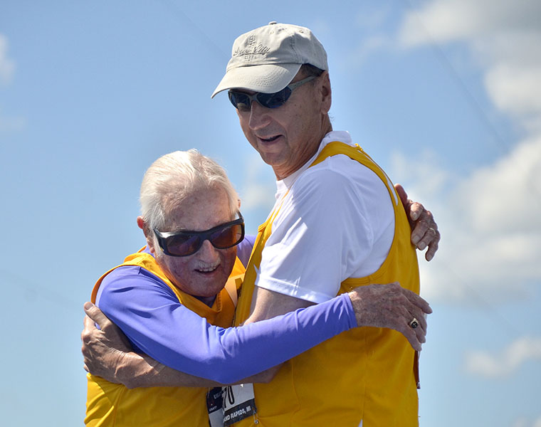 Champion Goldy and David RRRR embrace at finish of 100-meter dash.