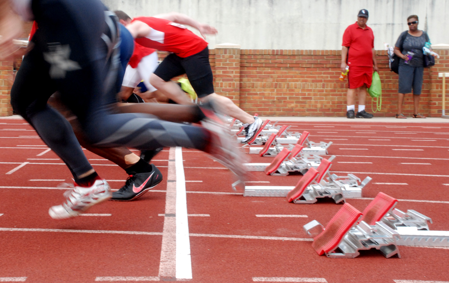 An M35 field blasts off behind white tape, marking true 100-meter start at Wake Forest.