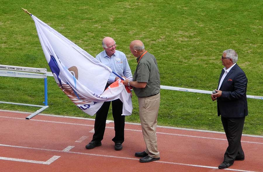 Lyon's LOC Prez Marcel Ferrari  watches Stan hand WMA flag to Perth's Robert Schickert .