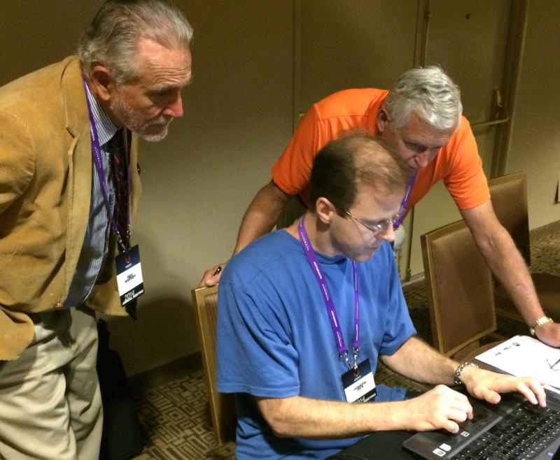 Rex (left) and Jim Flanik look over the shoulder of MTF Secretary Joseph Ols.