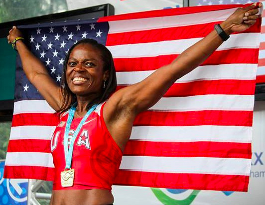 Ruthlyn Greenfield-Webster shows colors after winning gold in W40 triple jump.