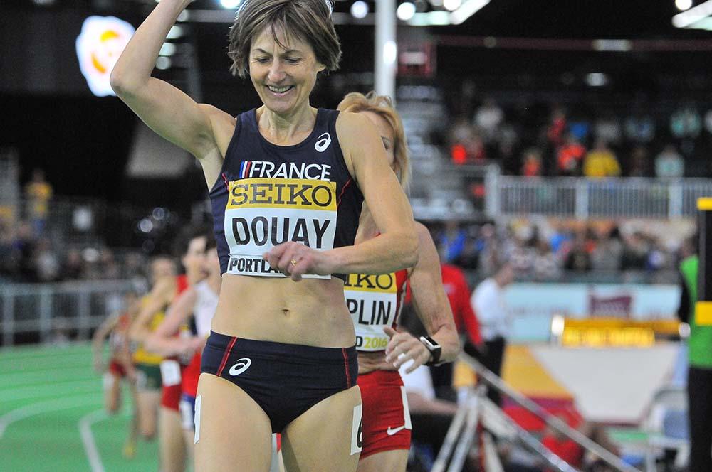 Helene Marie Douay of France celebrates winning the W55 race in 2:37.30,