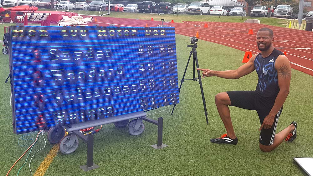 Allen kneels beside results sign of 49.12 M45 sprinters bow to him.